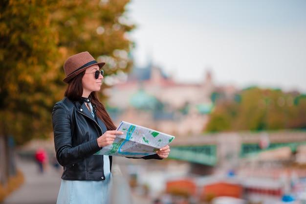 Felice giovane donna con una mappa della città in città. donna turistica di viaggio con la mappa all'aperto durante le vacanze in europa.