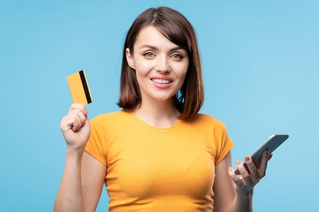 Felice giovane donna contemporanea cliente che mostra la carta di plastica durante lo scorrimento delle promozioni in smartphone