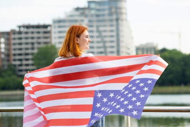 Felice giovane donna dai capelli rossi con bandiera nazionale usa sulle spalle in piedi all'aperto.