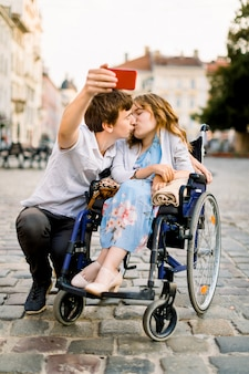 Felice giovane donna disabile in sedia a rotelle che bacia con il suo giovane ragazzo e sorride mentre prende selfie con lui nella città