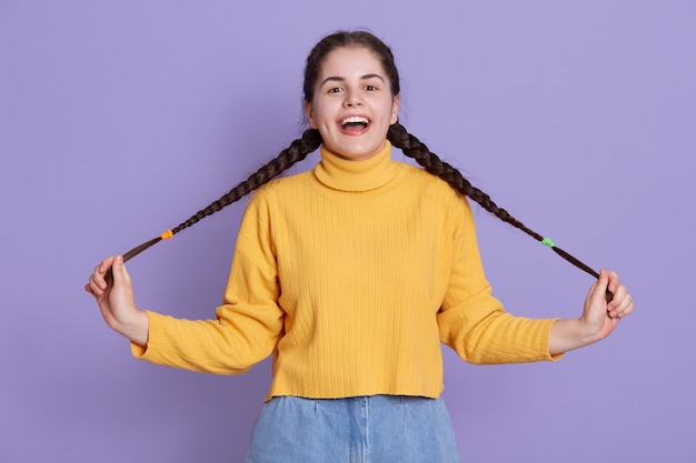 Felice giovane donna eccitata con i capelli lunghi scuri, ha le trecce, tenendo e diffondendo le code da parte