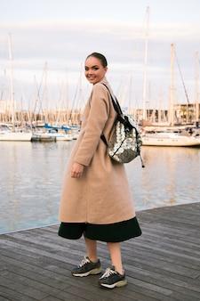 Felice giovane donna elegante che cammina allo yacht club di lusso di barcellona, indossando scarpe da ginnastica cappotto e zaino, tempo turistico di mezza stagione.