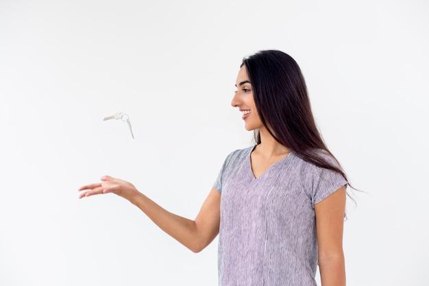 Felice giovane donna gettando le chiavi della macchina o di casa