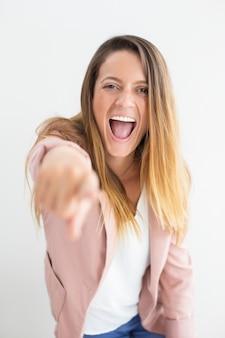 Felice giovane donna gridando e puntando alla fotocamera