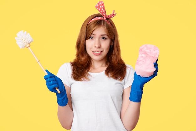 Felice giovane donna in abiti casual, detiene pennello e mop, pubblicizza prodotti per la pulizia