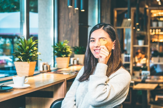 Felice giovane donna in un maglione caldo con una tazza di caffè e un biscotto seduto da una finestra