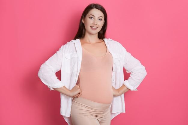 Felice giovane donna incinta in buona salute in piedi con le mani sui fianchi
