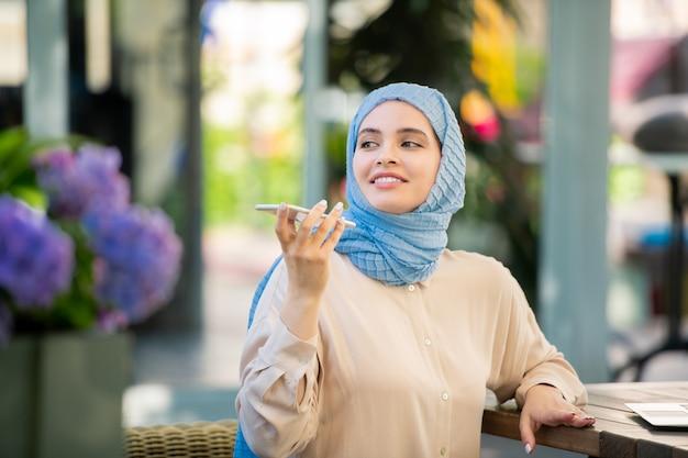 Felice giovane donna la registrazione di un messaggio vocale sullo smartphone mentre era seduto in ambiente urbano