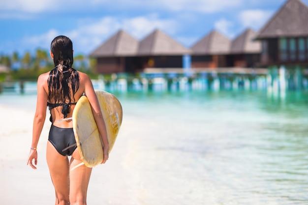 Felice giovane donna surf in spiaggia con una tavola da surf
