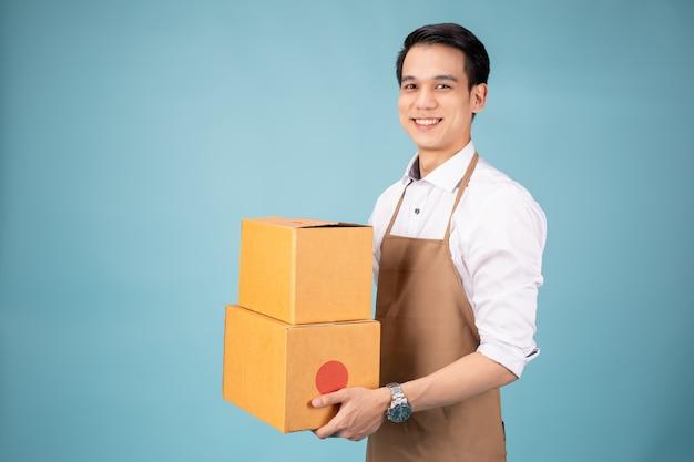Felice giovane fattorino in piedi con scatola pacco postale