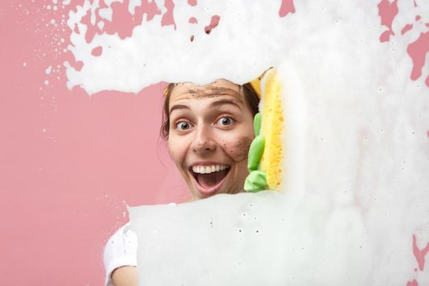 Felice giovane femmina emotiva con lo sporco sul viso guardando in eccitazione mentre fa le faccende domestiche, pulire le stanze nel suo appartamento, lavare le finestre, usare prodotti chimici e straccio