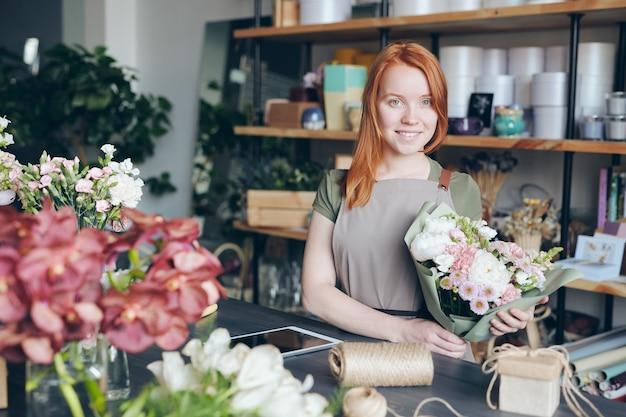 Felice giovane fioraio attraente rossa in grembiule che tiene bellissimo bouquet mentre si lavora nel proprio negozio