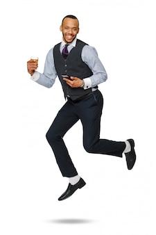 Felice giovane imprenditore africano che salta in alto e tenendo il caffè per andare e telefono isolato su bianco.