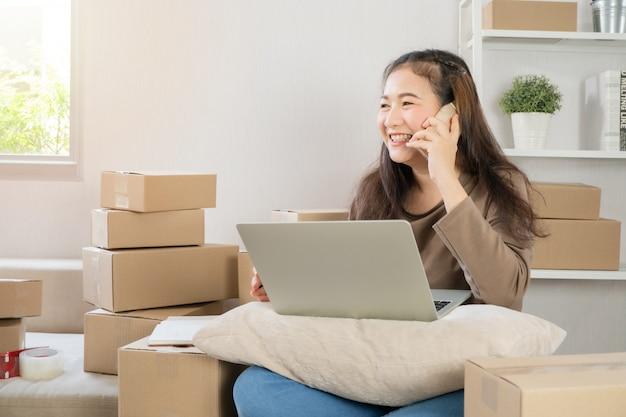 Felice giovane imprenditore asiatico, parlando sullo smartphone con il cliente per ordine tack