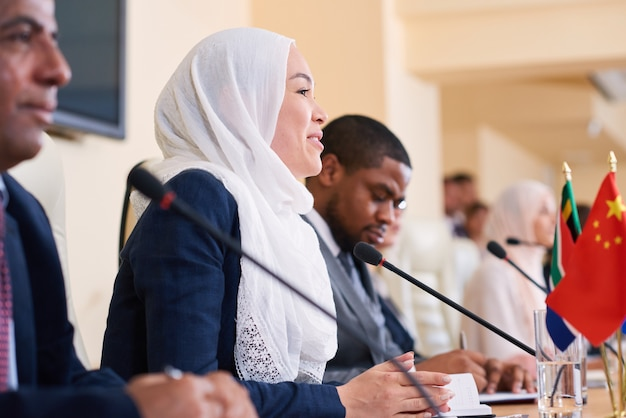 Felice giovane imprenditrice musulmana in hijab e abbigliamento formale a parlare con i colleghi stranieri alla conferenza