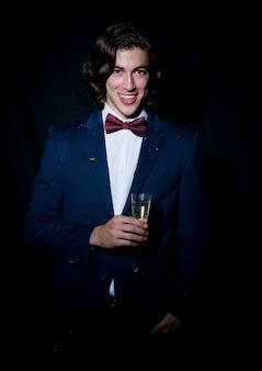 Felice giovane in piedi con un bicchiere di champagne