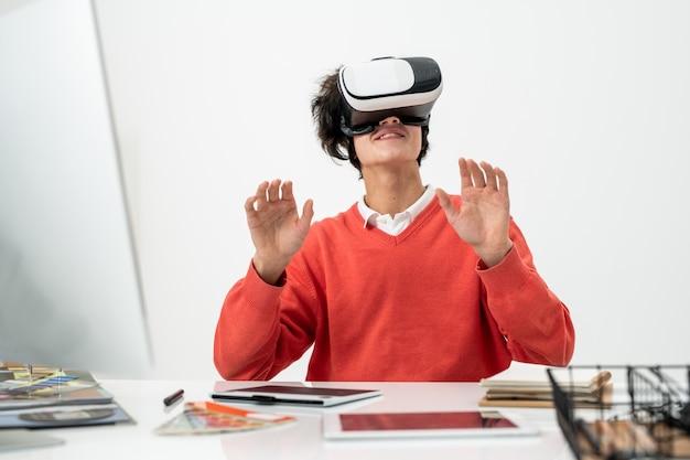 Felice giovane libero professionista in abbigliamento casual e auricolare vr seduto alla scrivania e toccando il display virtuale durante la visione di video