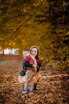 Felice giovane madre che gioca e si diverte con il suo piccolo figlio bambino nella calda giornata autunnale nel parco