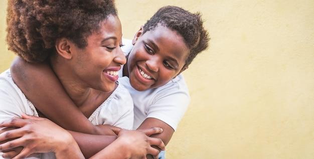 Felice giovane madre che si diverte con il suo bambino - figlio che abbraccia la sua mamma all'aperto - concetto di connessione familiare, maternità, amore e teneri momenti - focus sul volto del ragazzo