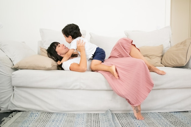 Felice giovane mamma bruna posa sul divano e abbracciare ragazzino con amore.