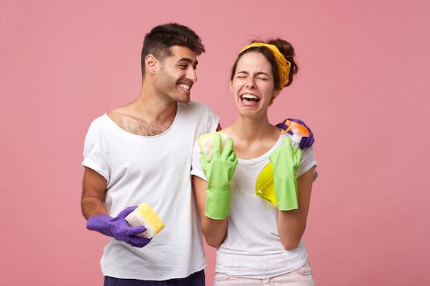 Felice giovane maschio confortante disperata donna stressata in guanti protettivi che non ha voglia di lavare i piatti. uomo positivo bello che ride della sua fidanzata piangente triste che odia pulire