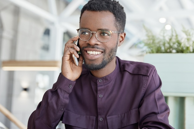 Felice giovane maschio dalla pelle scura con espressione positiva, ha un ampio sorriso, vestito con abiti formali, ha una conversazione telefonica con un partner commerciale