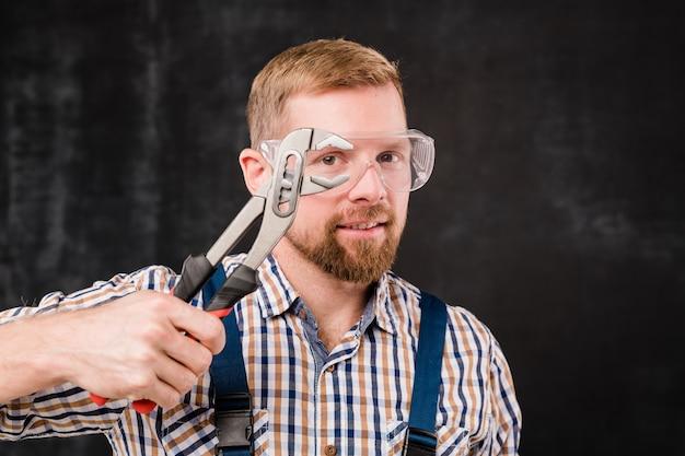 Felice giovane meccanico barbuto in occhiali protettivi, tute e maglietta che mostra il nuovo strumento manuale in isolamento su sfondo nero