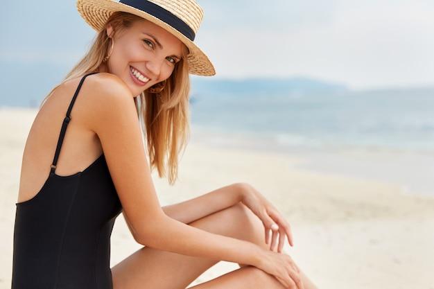 Felice giovane modello femminile con felice espressione sembra positivo, indossa un cappello estivo di paglia e costume da bagno nero, ha un ampio sorriso sul viso, ricrea sulla spiaggia sabbiosa vicino all'oceano o al mare.