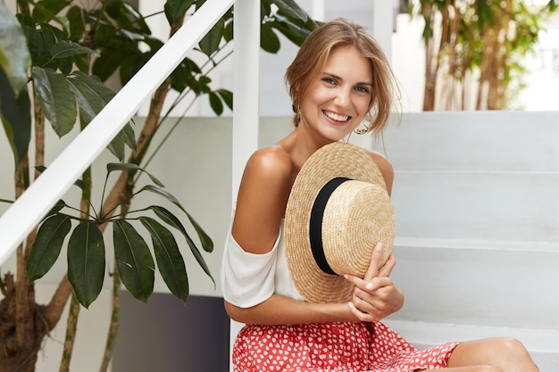 Felice giovane modello femminile ha un sorriso positivo tiene il cappello estivo di paglia e vestito con abiti alla moda, si siede alle scale con piantagioni esotiche, si riposa dopo aver passeggiato all'aperto al caldo soleggiato.