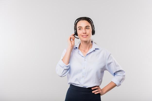 Felice giovane operatore elegante con auricolare che consulta i clienti online stando in piedi davanti alla telecamera in isolamento