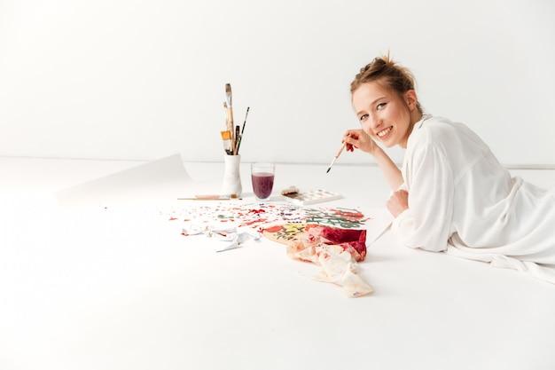 Felice giovane pittore caucasico signora nell'area di lavoro