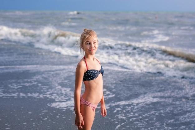 Felice giovane ragazza bionda si diverte in spiaggia da sogno con grandi onde bianche