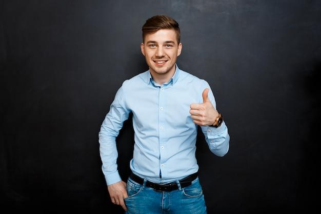 Felice giovane sorridente in camicia blu sopra la lavagna pollice in alto