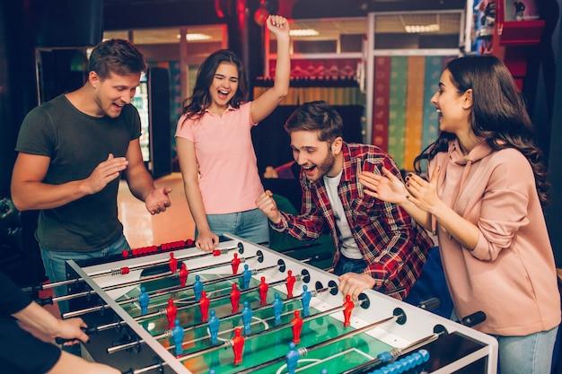 Felice giovane squadra felice stare al tavolo da calcio nella sala da gioco e tifo. ragazzo barbuto gioca con un altro essere umano. frieds lo circonda.