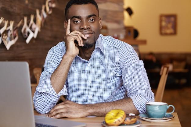 Felice giovane studente afro-americano che mangia caffè e ciambelle durante il pranzo al bar