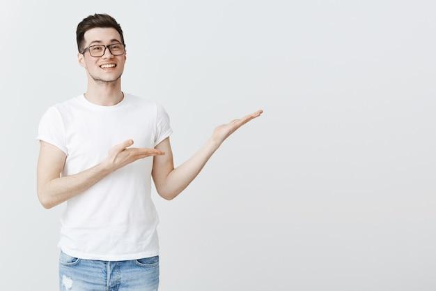 Felice giovane studente di college che indica le mani a destra