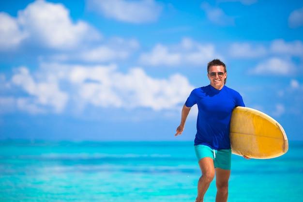 Felice giovane surf uomo che corre in spiaggia con una tavola da surf