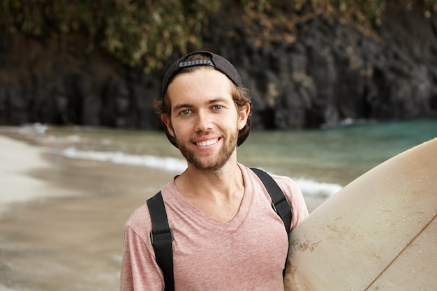 Felice giovane surfista in snapback guardando e sorridendo allegramente dopo aver vinto la gara sportiva tra i surfisti, tenendo la sua tavola da surf bianca sotto il braccio