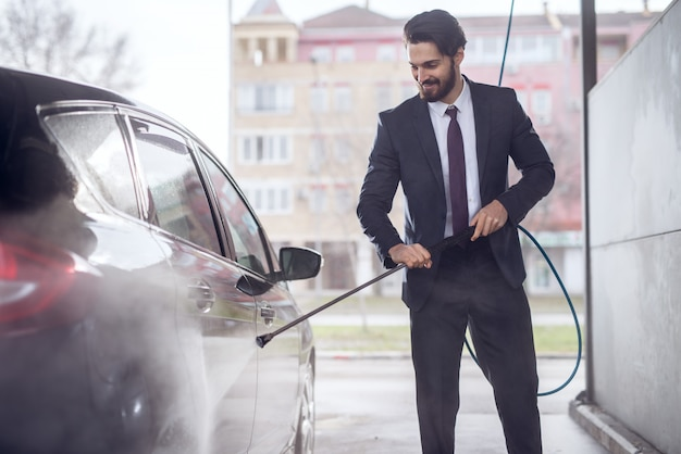Felice giovane uomo elegante elegante soddisfatto concentrato in un abito lavare la macchina con una pistola ad acqua sulla stazione di lavaggio auto self-service.