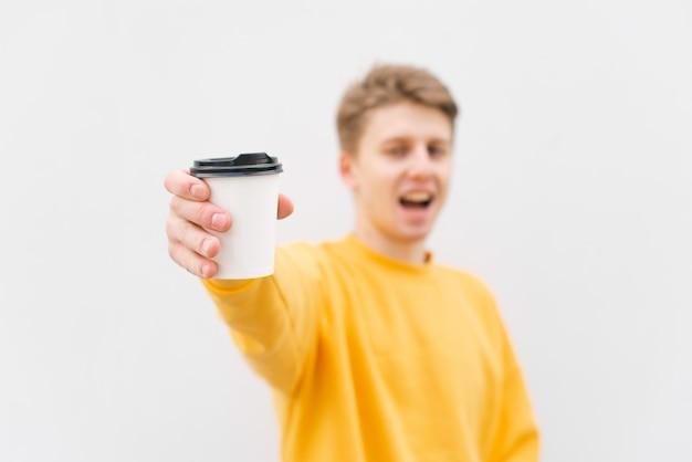 Felice giovane uomo in una maglietta bianca tiene una tazza di caffè in mano