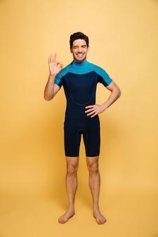 Felice giovane uomo vestito in costume da bagno che mostra il gesto giusto.