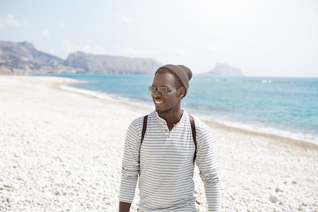 Felice giovane viaggiatore afroamericano in elegante cappello e occhiali da sole con una bella passeggiata lungo la spiaggia, godendo di tempo soleggiato e splendide viste. giovane uomo di colore attraente che posa nel paesaggio del mare