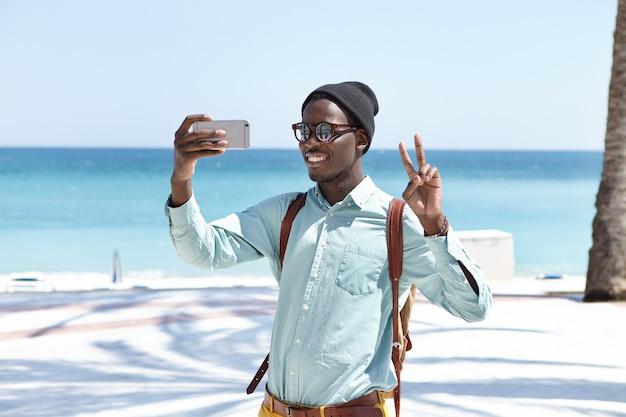 Felice giovane viaggiatore maschio con zaino che guarda e sorride alla macchina fotografica sul suo smartphone