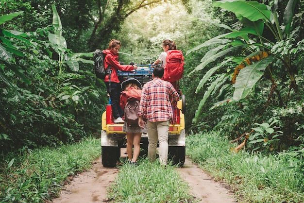 Felice giovani asiatici viaggiatori con 4wd unità auto fuori strada nella foresta, giovane coppia a piedi con zaini e altri due stanno godendo su 4wd drive car. giovane razza mista razza asiatica donna e uomo.