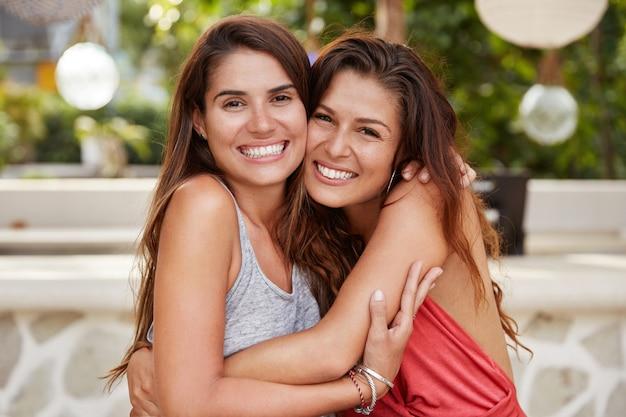 Felice giovani migliori amiche con un sorriso splendente, un aspetto piacevole e attraente, abbracciati e siedono vicini l'uno all'altro