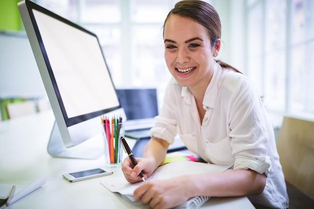 Felice graphic designer scrivendo sul libro alla scrivania