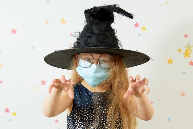 Felice halloween . bambina in costume da carnevale delle streghe e maschera protettiva per il viso.