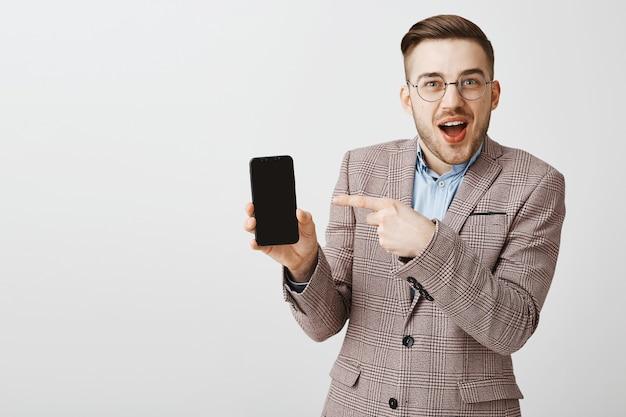 Felice imprenditore maschio in tuta puntare il dito sul ghiaione dello smartphone, mostrando l'applicazione mobile