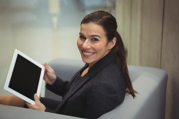 Felice imprenditrice seduto sul divano e utilizzando la tavoletta digitale