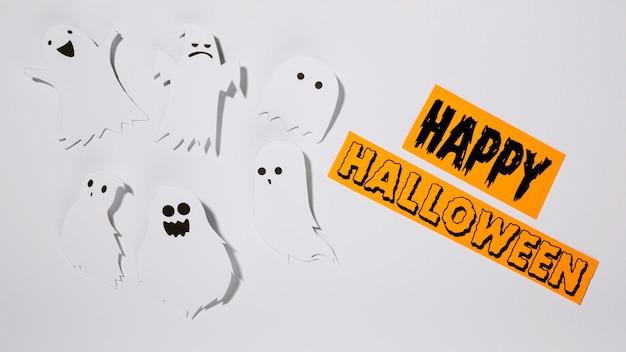 Felice iscrizione di halloween con fantasmi di carta
